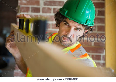 Tradesman leveling wooden plank at construction site - Stock Photo