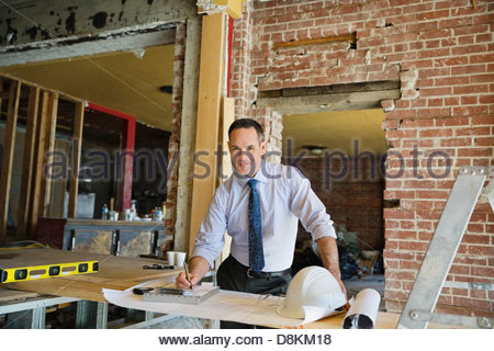 Portrait of male architect writing notes on work order at construction site - Stock Photo