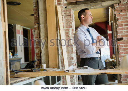 Side view of male architect standing at construction site - Stock Photo