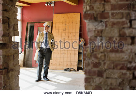 Full length view of male architect standing at construction site - Stock Photo