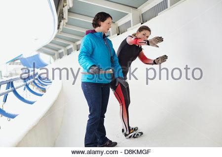 Female skeleton athlete with coach inspecting track - Stock Photo