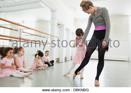 Female ballet instructor teaching children in ballet studio - Stock Photo