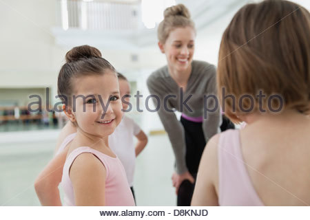 Portrait of girl with friends and instructor in ballet studio - Stock Photo