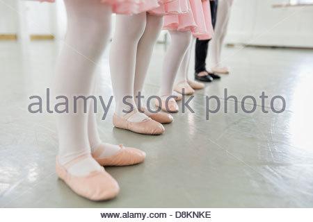 Line of children's feet in ballet slippers in ballet studio - Stock Photo