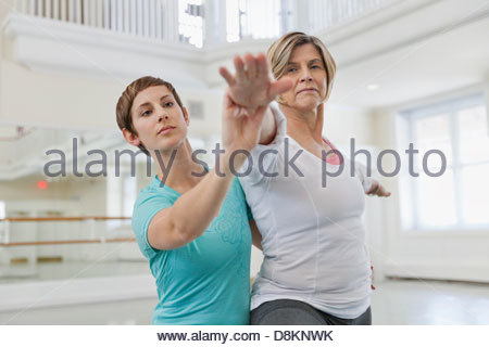 Woman instructor assisting student with yoga pose in yoga studio - Stock Photo