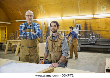 Portrait of carpenters in woodworking shop - Stock Photo