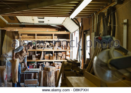 Woodworker organizing equipment in workshop - Stock Photo