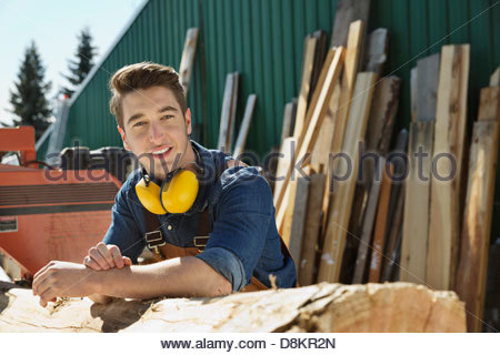 Portrait of woodworker leaning on log - Stock Photo