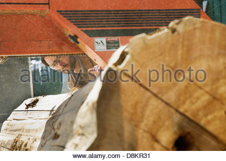Woodworker looking at large log going through band saw - Stock Photo