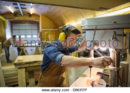 Young male carpenter using drill press in workshop - Stock Photo