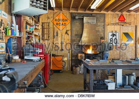 Welder working at blacksmith forge in workshop - Stock Photo