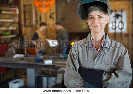 Confident female welder in protective work wear - Stock Photo
