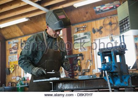 Welder in protective work wear working at workshop - Stock Photo