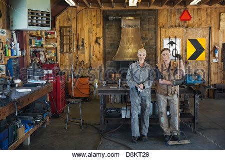 Portrait of metal smiths standing in workshop - Stock Photo