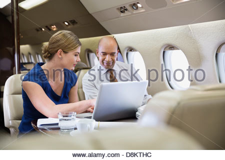 Business colleagues looking at laptop in airplane - Stock Photo