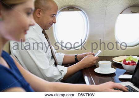 Business colleagues using technology in airplane - Stock Photo