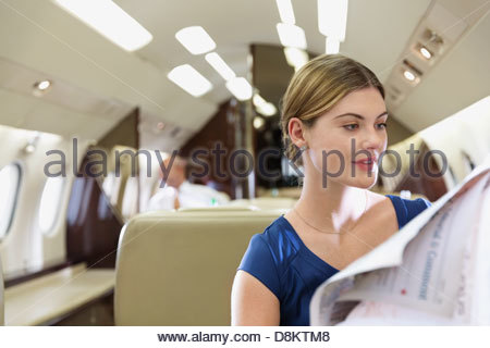 Businesswoman reading newspaper in airplane - Stock Photo