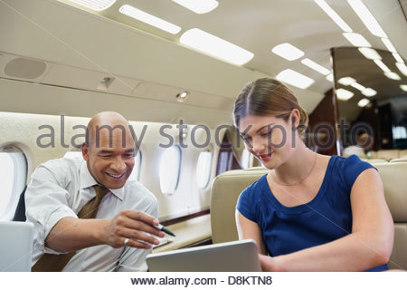Businesswoman showing digital tablet to colleague in airplane - Stock Photo
