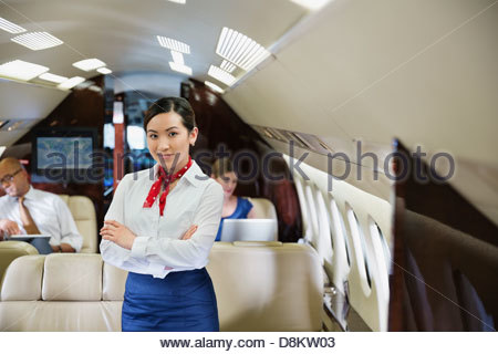Portrait of flight attendant standing with arms crossed in airplane - Stock Photo