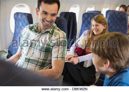Father with children traveling in airplane - Stock Photo