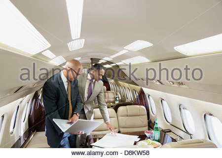 Businessmen with laptop discussing blueprints in airplane - Stock Photo