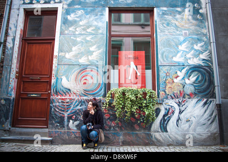 Girl near a beautiful drawing on front of a typical house Belgian in Patershol neighborhood in Ghent - Stock Photo