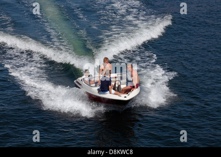 Young men sailing rather fast in a speedboat in the port of Copenhagen heading towards Knippelsbro bridge. - Stock Photo