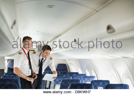 Male pilot and co-pilot looking out window in airplane cabin - Stock Photo