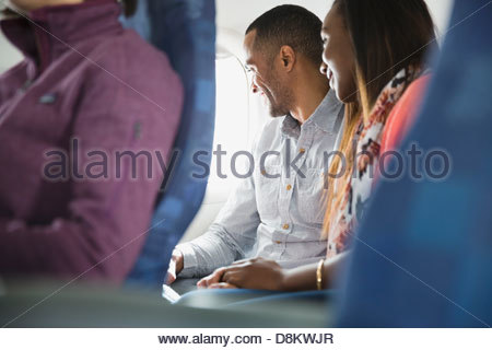Couple looking out window in airplane - Stock Photo