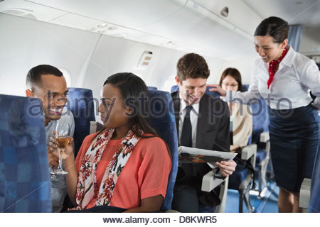 Couple relaxing with a drink in airplane - Stock Photo