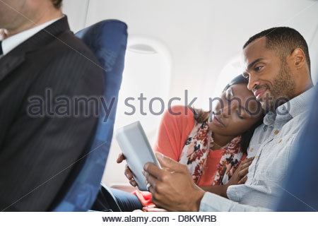 Couple using digital tablet in airplane - Stock Photo