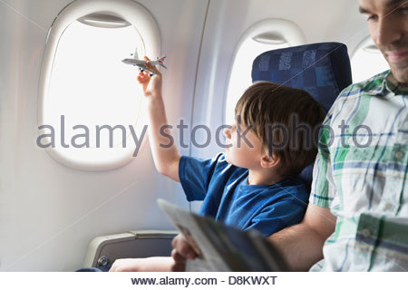Boy playing with toy plane in airplane - Stock Photo