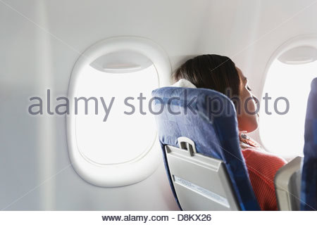 Woman sleeping in airplane - Stock Photo
