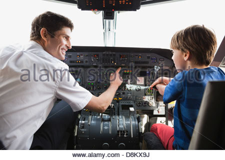 Male pilot explaining control panel to boy in airplane cockpit - Stock Photo