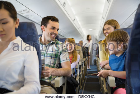 Smiling family traveling in airplane - Stock Photo