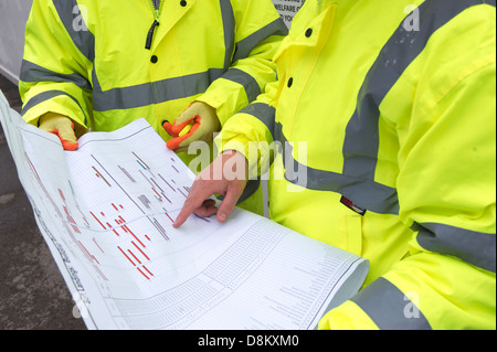 Two construction workers examine plans at a building site. - Stock Photo