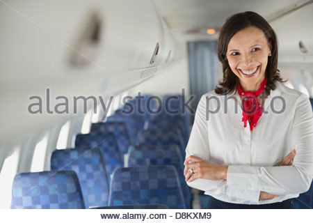 Flight attendant standing with arms crossed in airplane cabin - Stock Photo