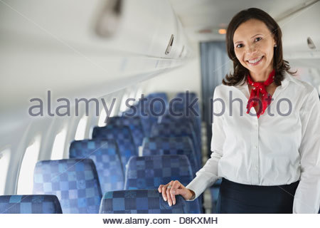 Portrait of flight attendant standing in airplane cabin - Stock Photo