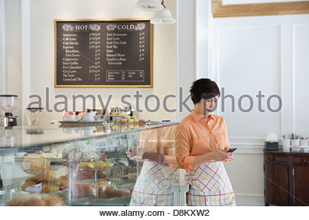 Female small business owner working in coffee shop - Stock Photo