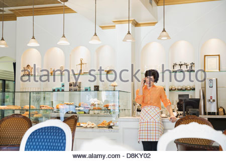 Female small business owner talking on mobile phone in coffee shop - Stock Photo