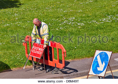 workman in yellow jacket leaning over red barrier placing a footway closed sign on footpath - Stock Photo