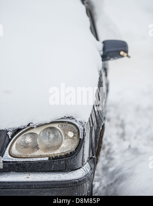silver car filled up with snow in winter - Stock Photo