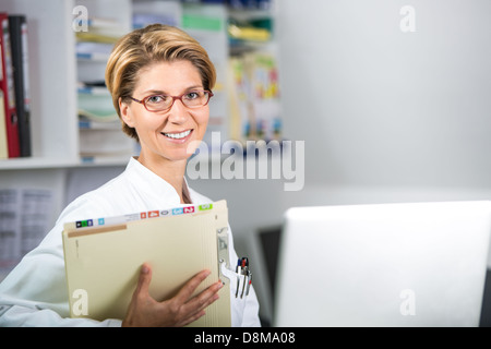Young doctor with medical records and laptop - Stock Photo