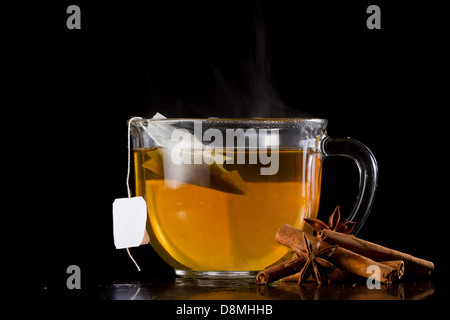hot tea served on a dark background with star anise and cinnamon sticks - Stock Photo