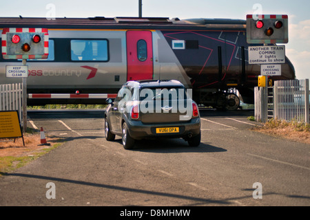 Car waiting at level crossing while train passes - Stock Photo