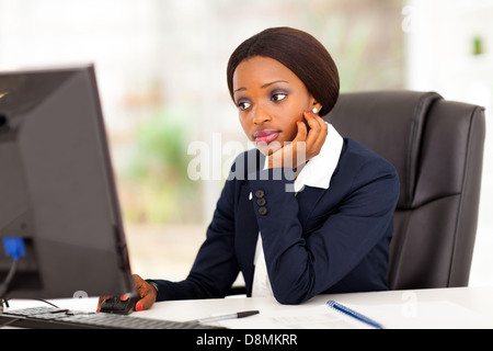 thoughtful African American businesswoman looking at computer screen in office - Stock Photo