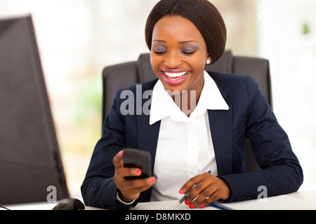 happy African American businesswoman reading sms in office - Stock Photo