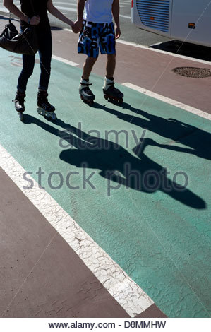 Roller skating lovers holding hands, on the Promenade des Anglais in Nice, southern France. - Stock Photo