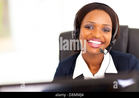 happy African American telephonist in front of computer - Stock Photo