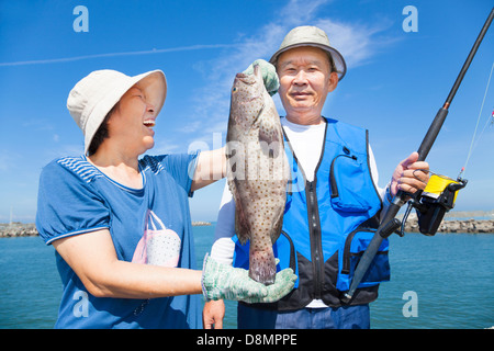 happy asian senior couple fishing and showing big grouper - Stock Photo